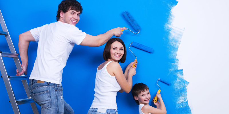 Young couple with their son painting the wall on blue color