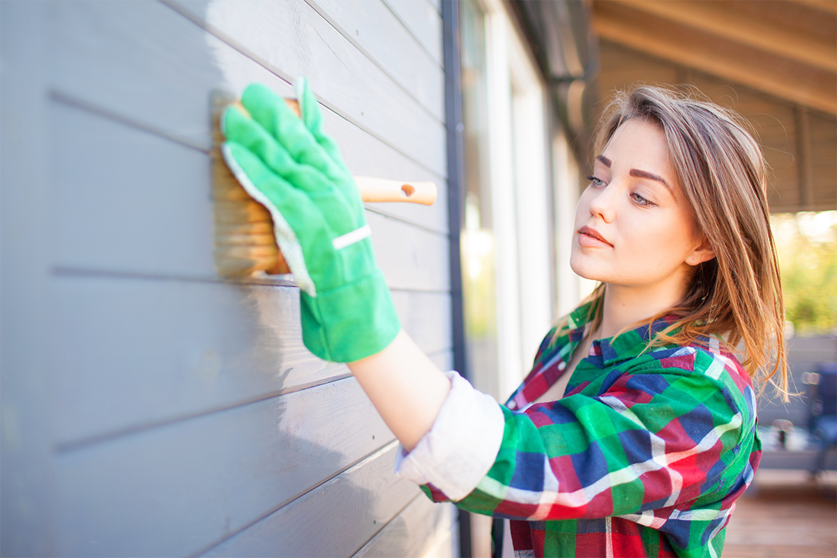 A woman painting wall wearing green gloves